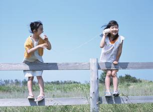 草原の柵につかまり糸電話で遊ぶ2人の日本人の女の子の写真素材 [FYI03208665]