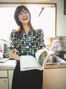 キッチンで本を広げる日本人女性の写真素材 [FYI03208701]