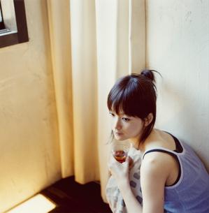 グラス持ちかがむ日本人女性の写真素材 [FYI03208708]