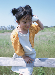 柵につかまり糸電話で遊ぶ日本人の女の子の写真素材 [FYI03208711]