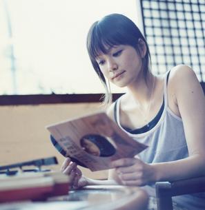 レコードジャケットを眺める日本人女性の写真素材 [FYI03208723]