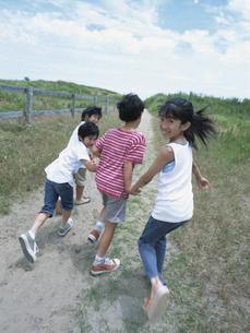 手をつないで走り出す男の子と女の子 日本人の写真素材 [FYI03208766]