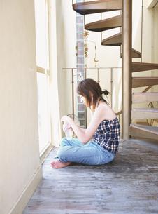 螺旋階段の側の窓辺に座る日本人女性の写真素材 [FYI03208857]