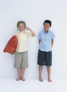 枕をかかえ敬礼する外国人の男の子と笑う日本人の男の子の写真素材 [FYI03208907]