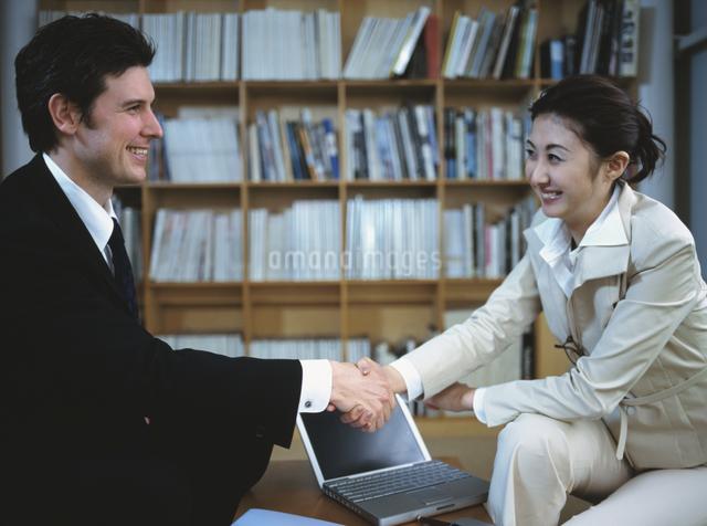 本棚の前で握手をするビジネスマン&ウーマンの写真素材 [FYI03208923]
