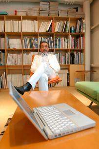 ノートパソコンといすに座る日本人男性の写真素材 [FYI03209056]