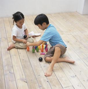 おもちゃのピンボールで遊ぶ男の子と女の子 日本人の写真素材 [FYI03209157]