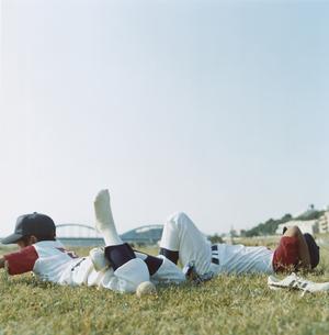 芝生に寝転ぶ2人の野球少年 日本人の写真素材 [FYI03209256]