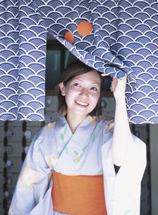 銭湯入り口の暖簾を開ける浴衣姿の日本人女性の写真素材 [FYI03209261]