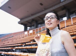 観客席でポップコーンを食べる40代の日本人女性の写真素材 [FYI03209263]