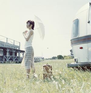 日傘を差した日本人女性とトレーラー近くに置かれたトランクの写真素材 [FYI03209309]