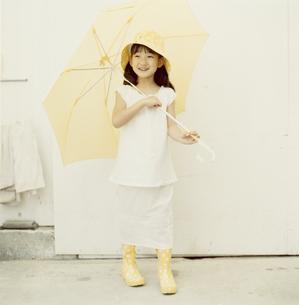 黄色い傘を差す長靴を履いた日本人の女の子の写真素材 [FYI03209322]