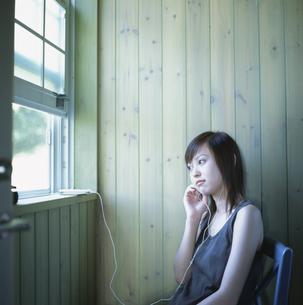 窓際の椅子に座りヘッドフォンで音楽を聴く日本人女性の写真素材 [FYI03209359]