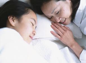 ベットで眠っている女の子と添い寝をするお母さんの写真素材 [FYI03209470]