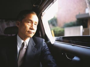 車内の後部座席に座る中高年ビジネスマンの写真素材 [FYI03209513]