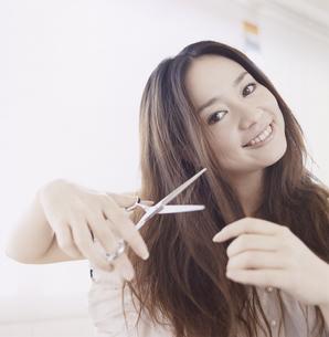 ハサミで髪を切る日本人女性の写真素材 [FYI03209524]