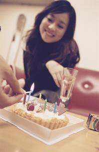 ローソクの点いたケーキを眺める日本人女性の写真素材 [FYI03209572]