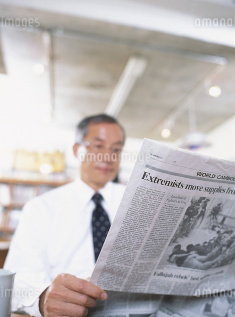 オフィスで新聞を読む中高年ビジネスマンの写真素材 [FYI03209582]