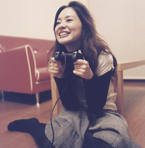 ゲームのコントローラーを握る日本人女性の写真素材 [FYI03209591]