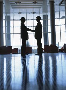 向き合う2人のビジネスマンのシルエットの写真素材 [FYI03209595]