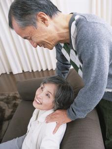 リビングで肩を揉むシニア夫婦の写真素材 [FYI03209672]