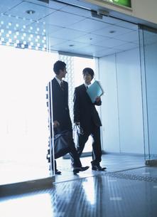 自動ドアから入ってくる2人の日本人ビジネスマンの写真素材 [FYI03209681]