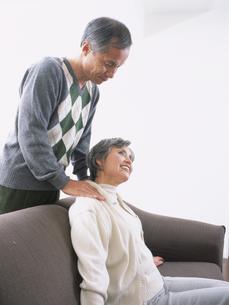 リビングで肩を揉むシニア夫婦の写真素材 [FYI03209693]
