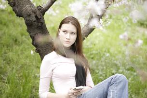桜の木の下で音楽を聴く女性の写真素材 [FYI03209806]