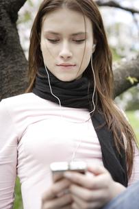 桜の木の下で音楽を聴く女性の写真素材 [FYI03209812]