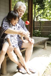 縁側で遊ぶおじいちゃんと孫の写真素材 [FYI03209893]