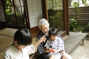縁側で遊ぶおじいちゃんと孫の写真素材 [FYI03209901]