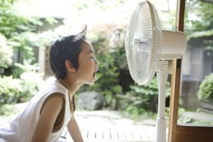 扇風機に顔を近づける男の子の写真素材 [FYI03209946]