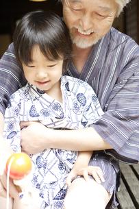 縁側で遊ぶおじいちゃんと孫の写真素材 [FYI03209984]