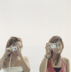 デジカメを構える20代女性2人の写真素材 [FYI03210121]