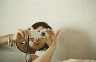 デジカメを構える20代女性の写真素材 [FYI03210129]