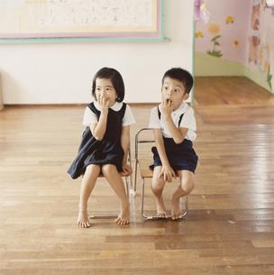 教室でイスに座っている園児2人の写真素材 [FYI03210139]