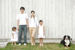 壁際に立つ家族と犬の写真素材 [FYI03210372]