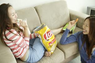 ポテトチップスを食べる女性2人の写真素材 [FYI03210845]