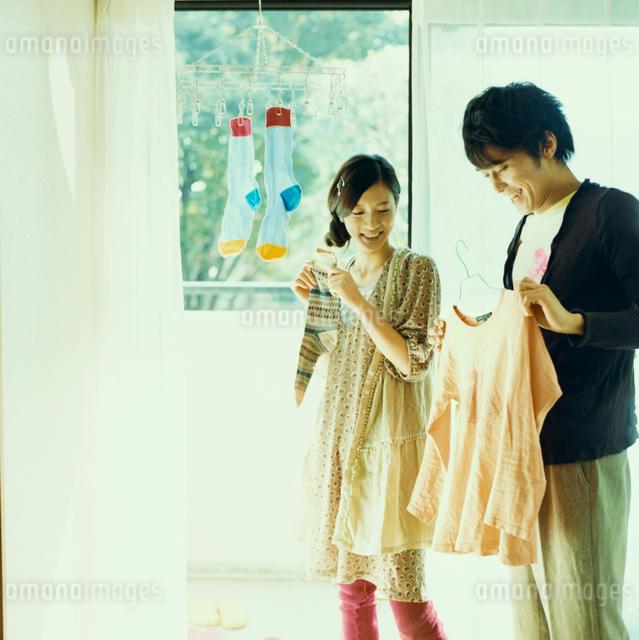 洗濯物を干すカップルの写真素材 [FYI03211237]