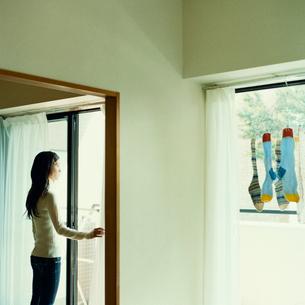 窓辺に立ち外を見つめる女性の写真素材 [FYI03211257]