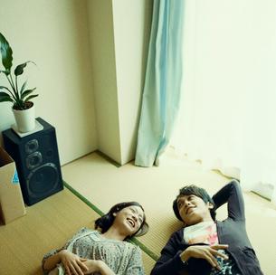 畳の部屋に寝転ぶカップルの写真素材 [FYI03211261]