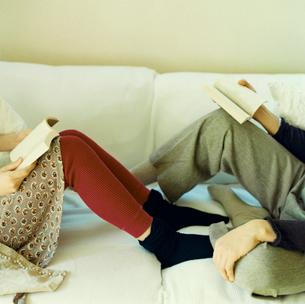 本を開いて座るカップルの足の写真素材 [FYI03211282]