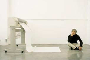 印刷機の前に座り考える中年男性の写真素材 [FYI03211353]
