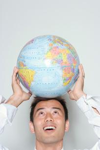地球儀を頭にのせる日本人ビジネスマンの写真素材 [FYI03211597]