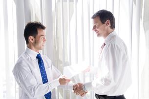オフィスで握手するビジネスマンの写真素材 [FYI03211603]