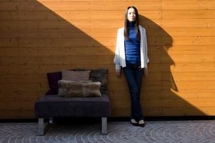 壁際に立つ女性の写真素材 [FYI03211989]