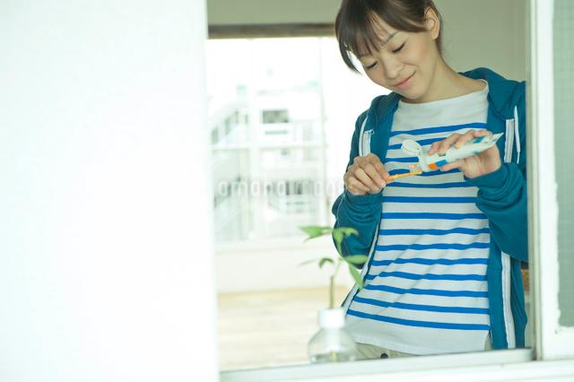 窓際で歯磨きをする女性の写真素材 [FYI03212340]