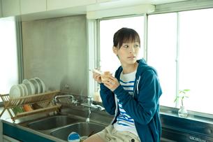 台所のシンクの上に座りプリンを食べる女性の写真素材 [FYI03212357]