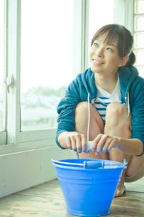 雑巾を絞りながら窓の外を見る女性の写真素材 [FYI03212375]