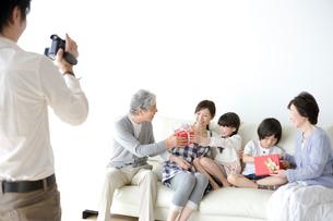 ソファに集まる三世代家族とビデオ撮影をする父の写真素材 [FYI03212460]